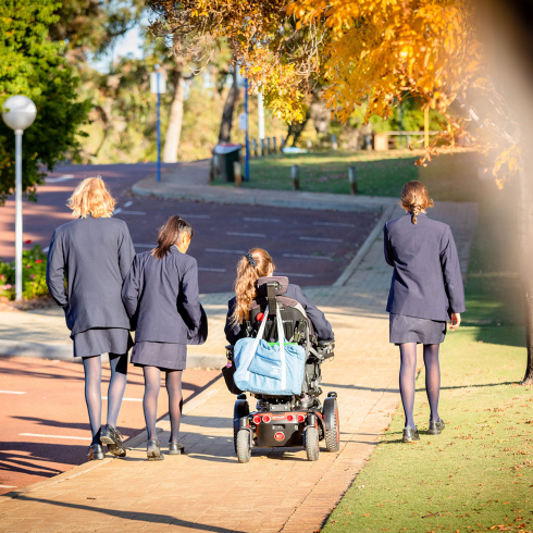 Alice driving her wheelchair along side three friends down a path leaving the school