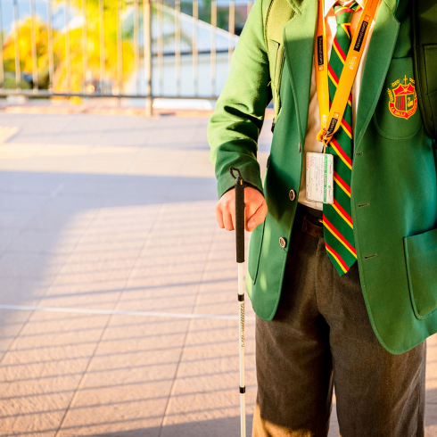 Male student wearing a his green school blazer and uniform holding his walking cane