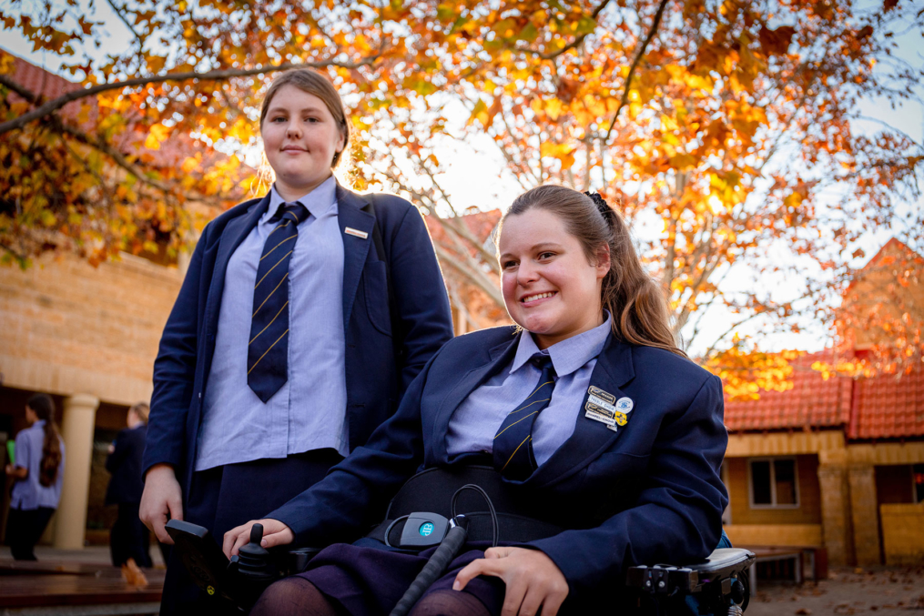 Alice in the courtyard sitting in her wheelchair next to her friend standing beside her