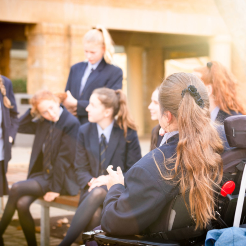 Alice sitting in her wheel chair talks to her friends in the school yard